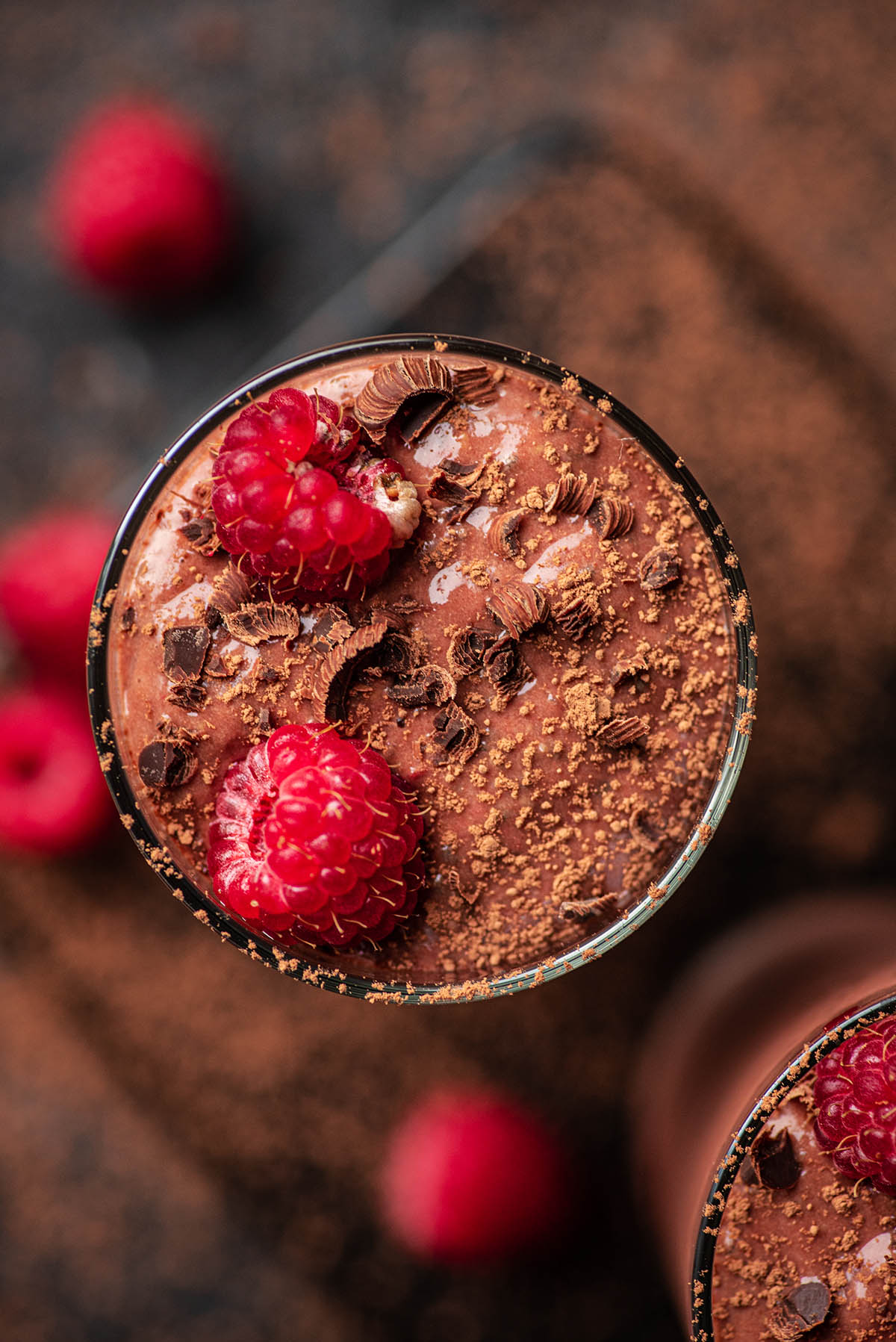 Chocolate raspberry protein shakes topped with chocolate, cocoa, and berries.
