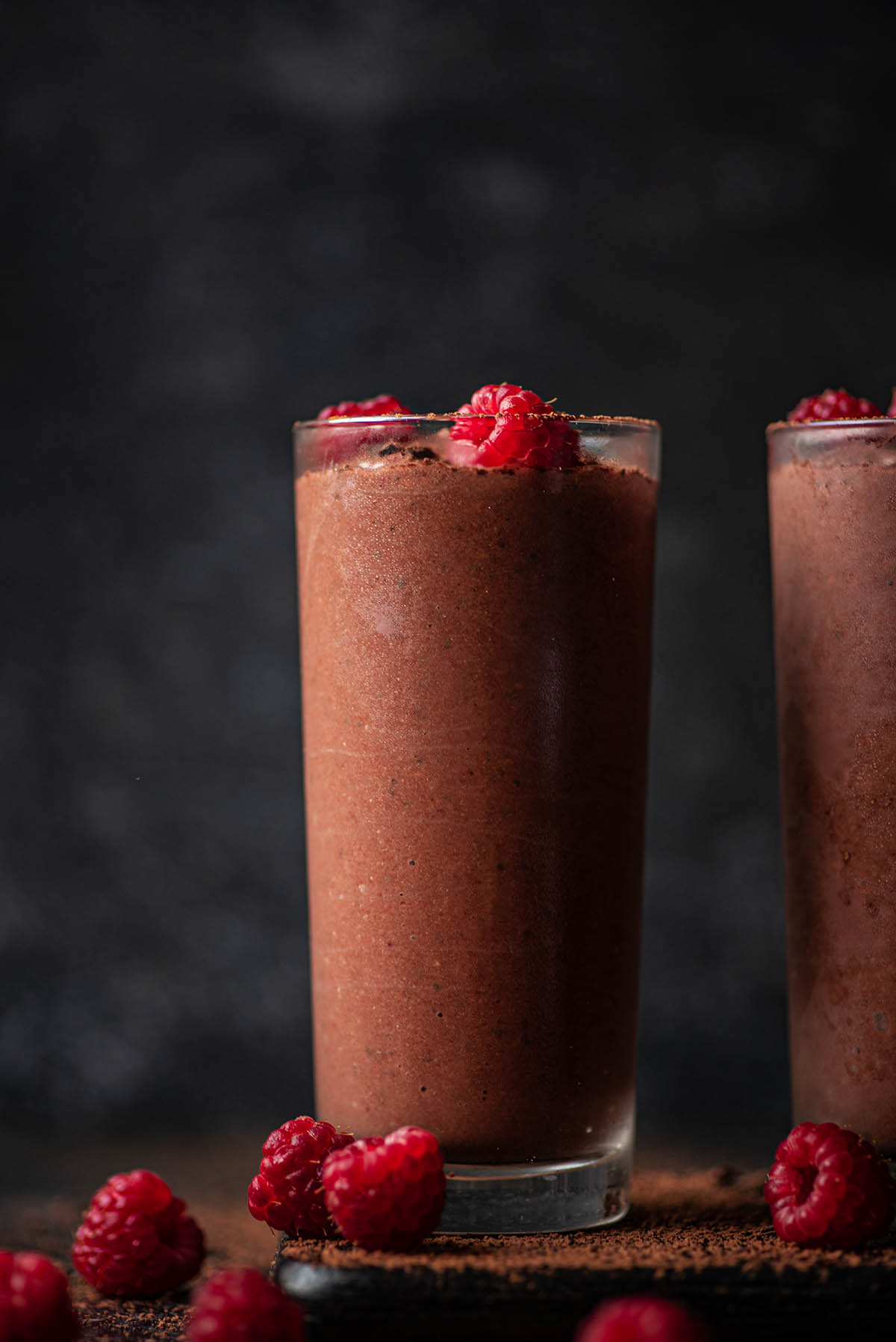 Two glasses of chocolate smoothie with raspberries.
