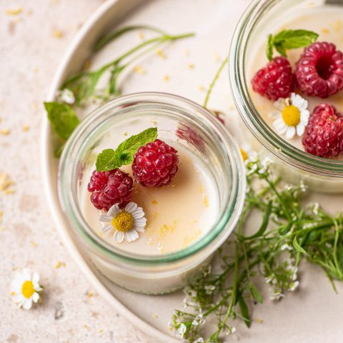 Two small glass jars filled with off-white pudding topped with berries.