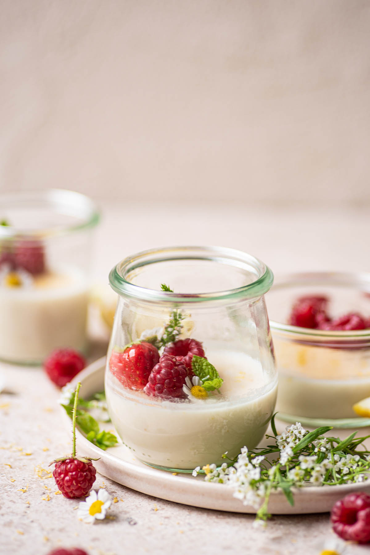 A half-full jar of panna cotta on a plate with berries and mint.