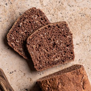 Two slices of dark rye bread with oats cut from a loaf.