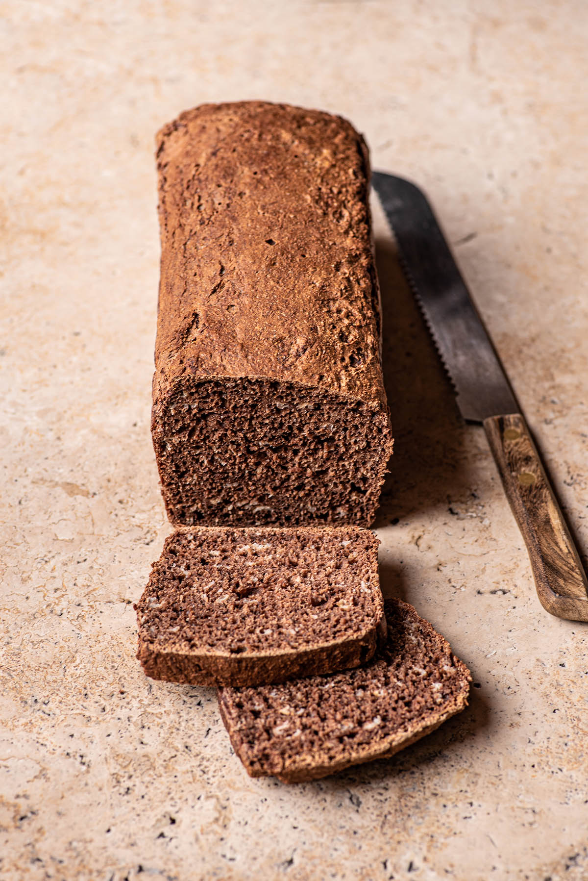 A loaf of dark rye bread with two slices cut.