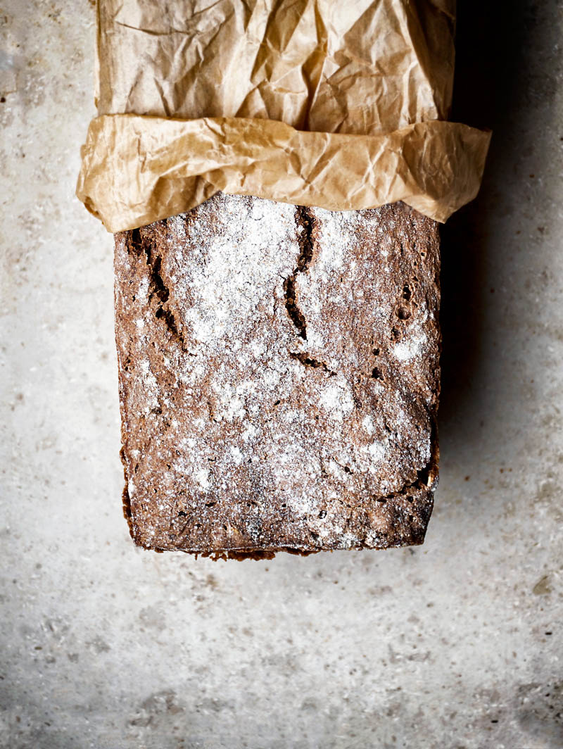 A loaf of dark rye bread halfway into a paper bag, top down view.