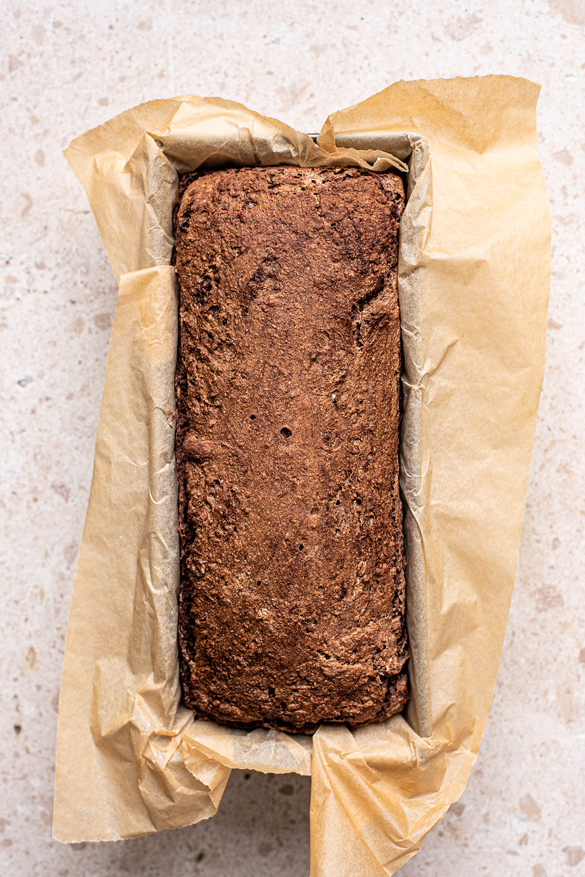 A baked loaf of rye bread in a paper-lined tin.