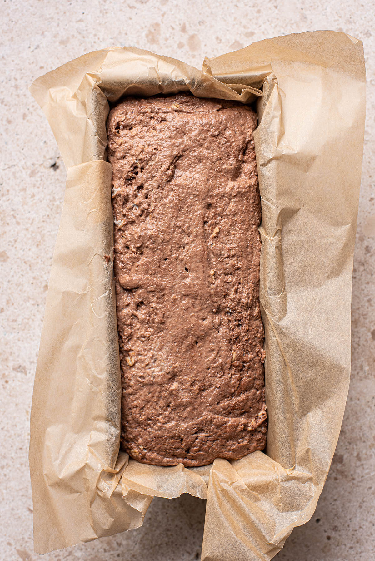 An unbaked loaf of rye bread in a paper-lined tin.