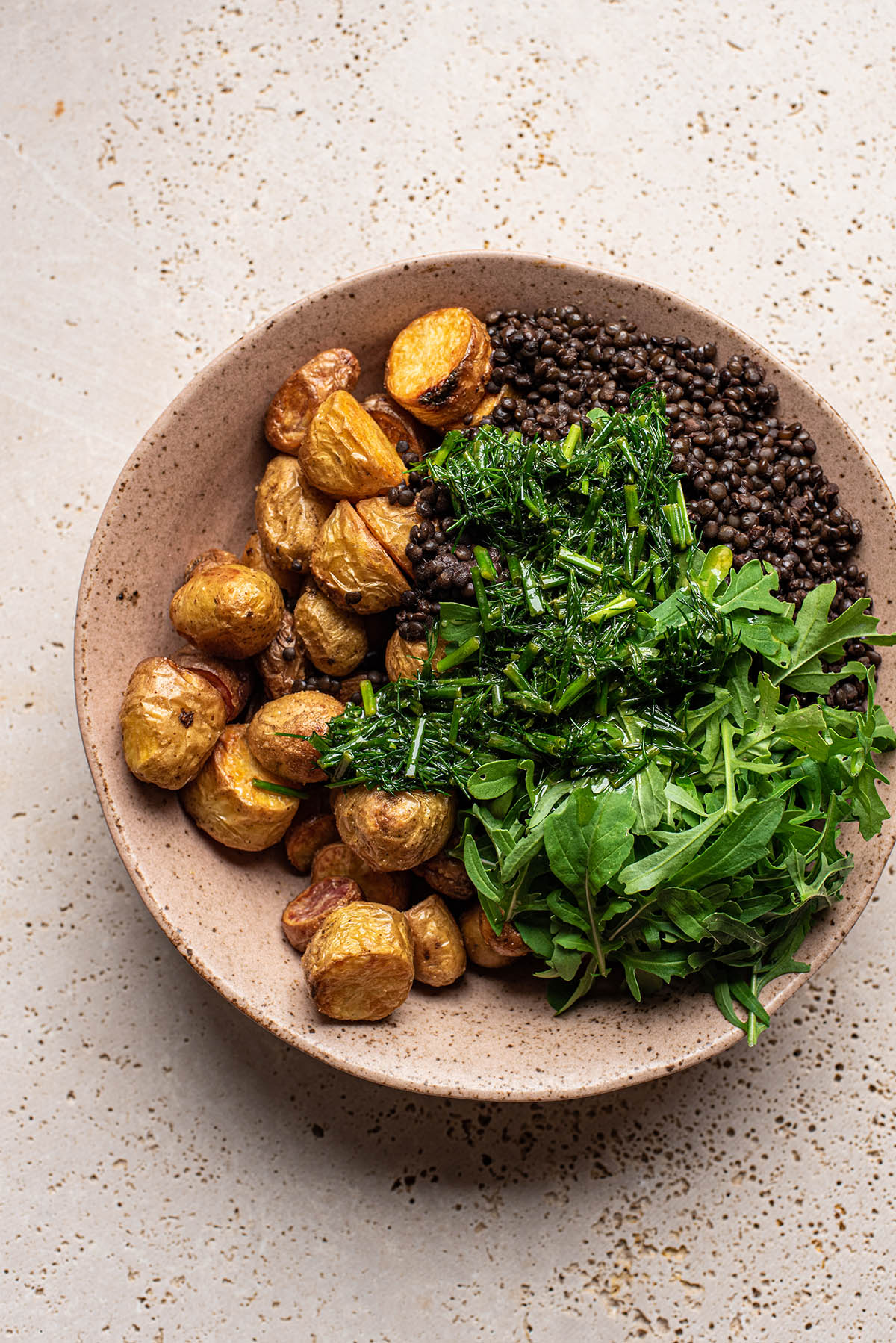 Roasted potatoes, lentils, greens, and herbs in a large bowl.