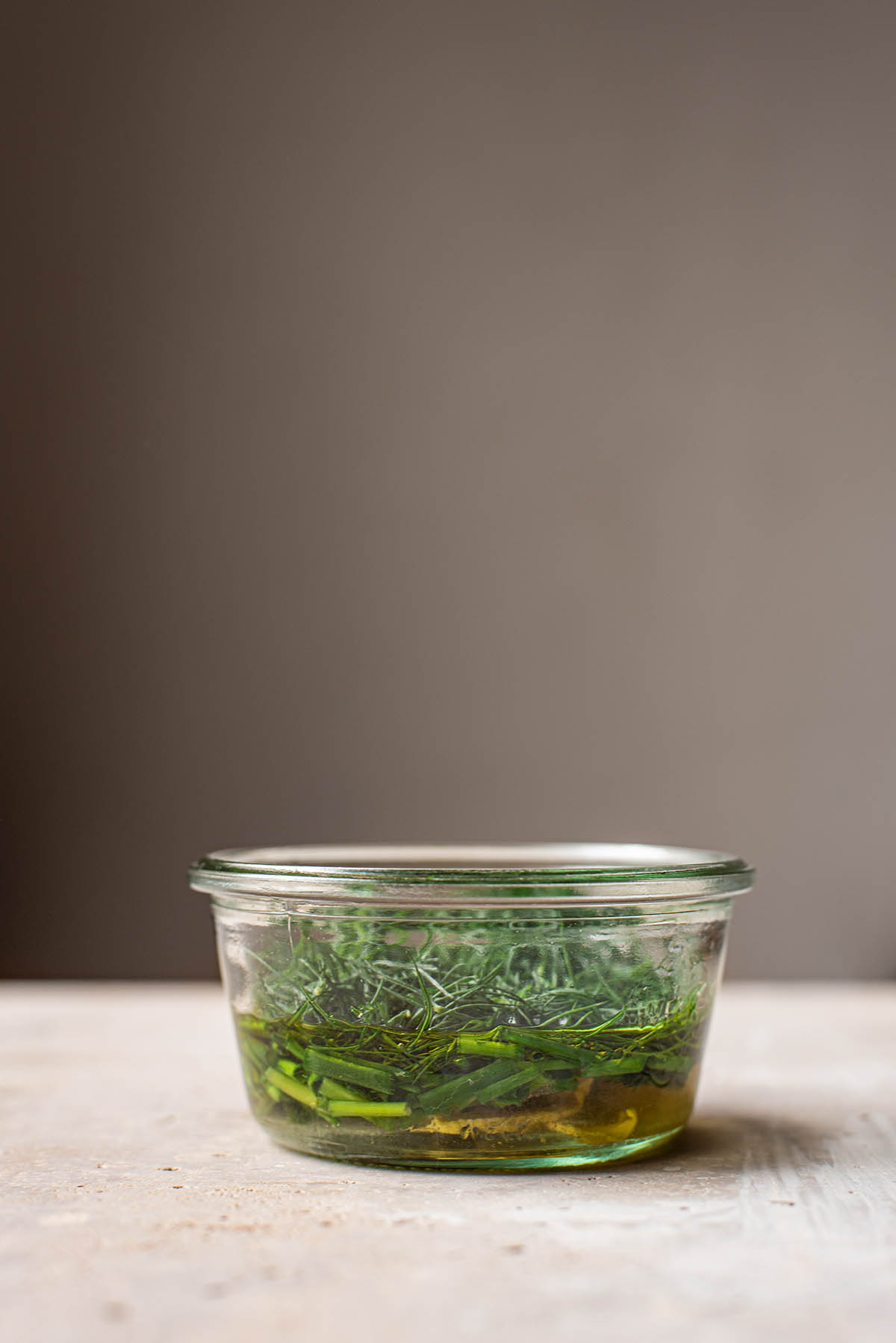 Herb vinaigrette in a glass jar before mixing.