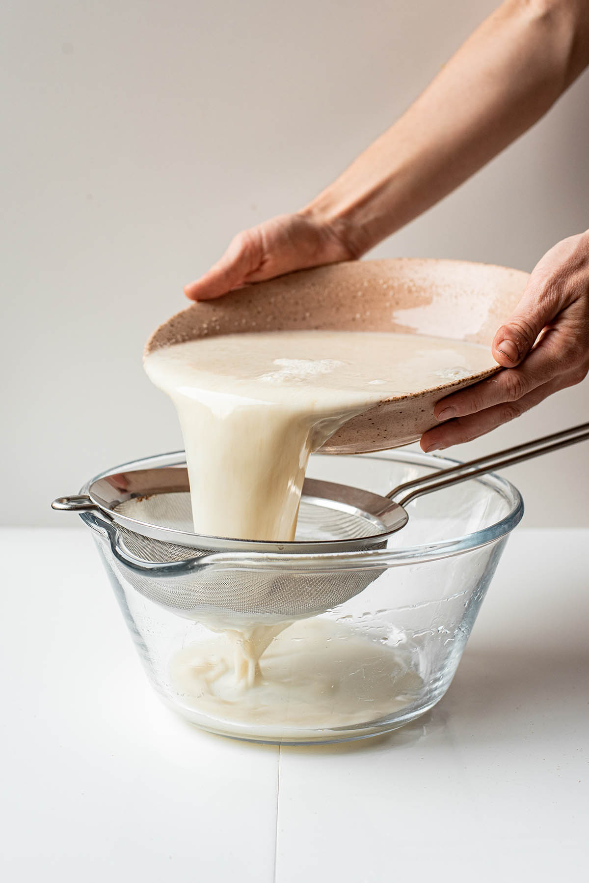Woman's hands pouring oat milk through a strainer into a bowl.