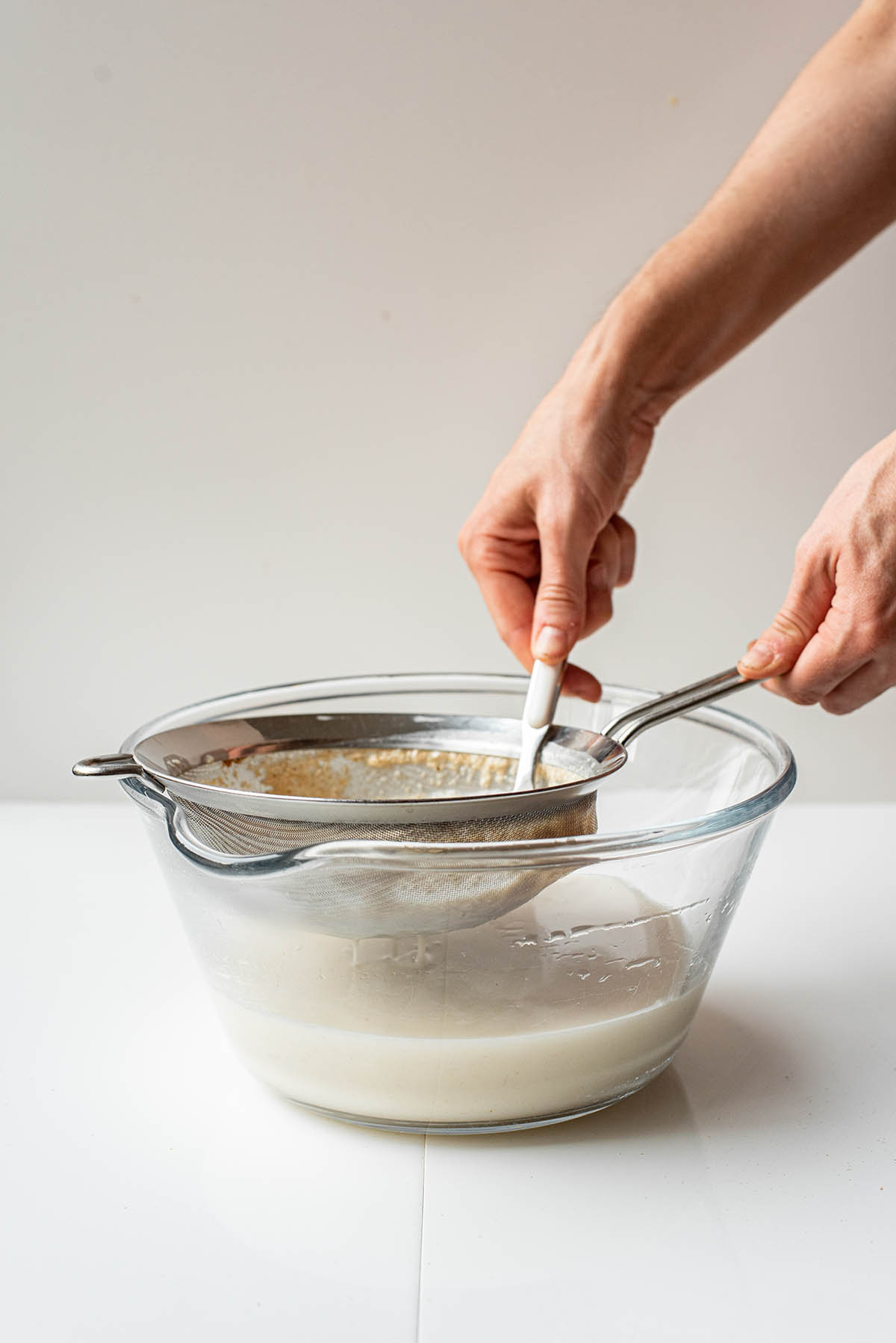 Woman's hands pushing oat milk through a strainer into a large bowl.