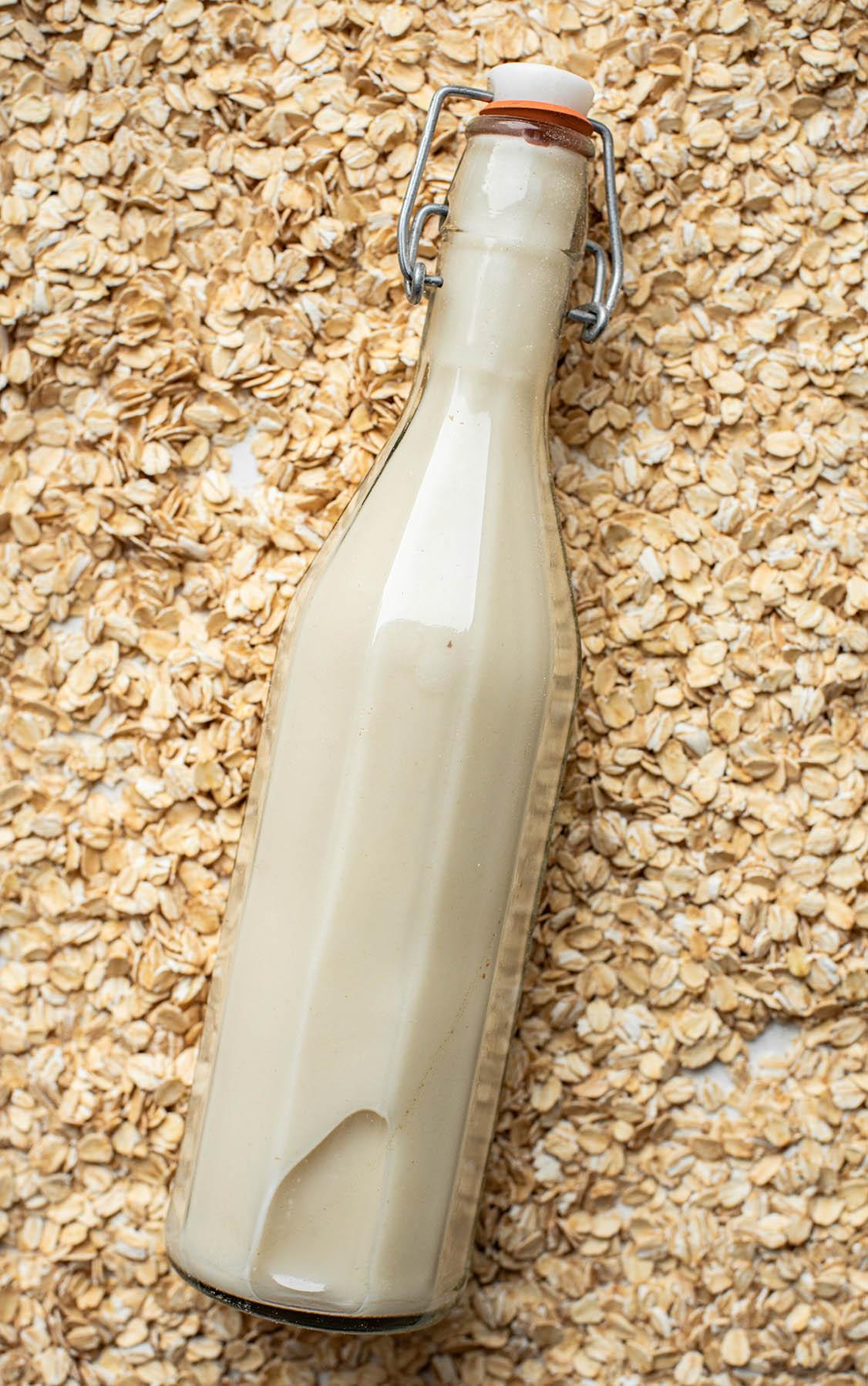 Oat milk in a flip-top glass bottle lying in a pile of oats.