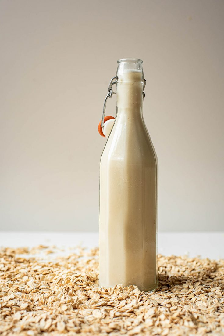 Oat milk in a flip-top glass bottle.