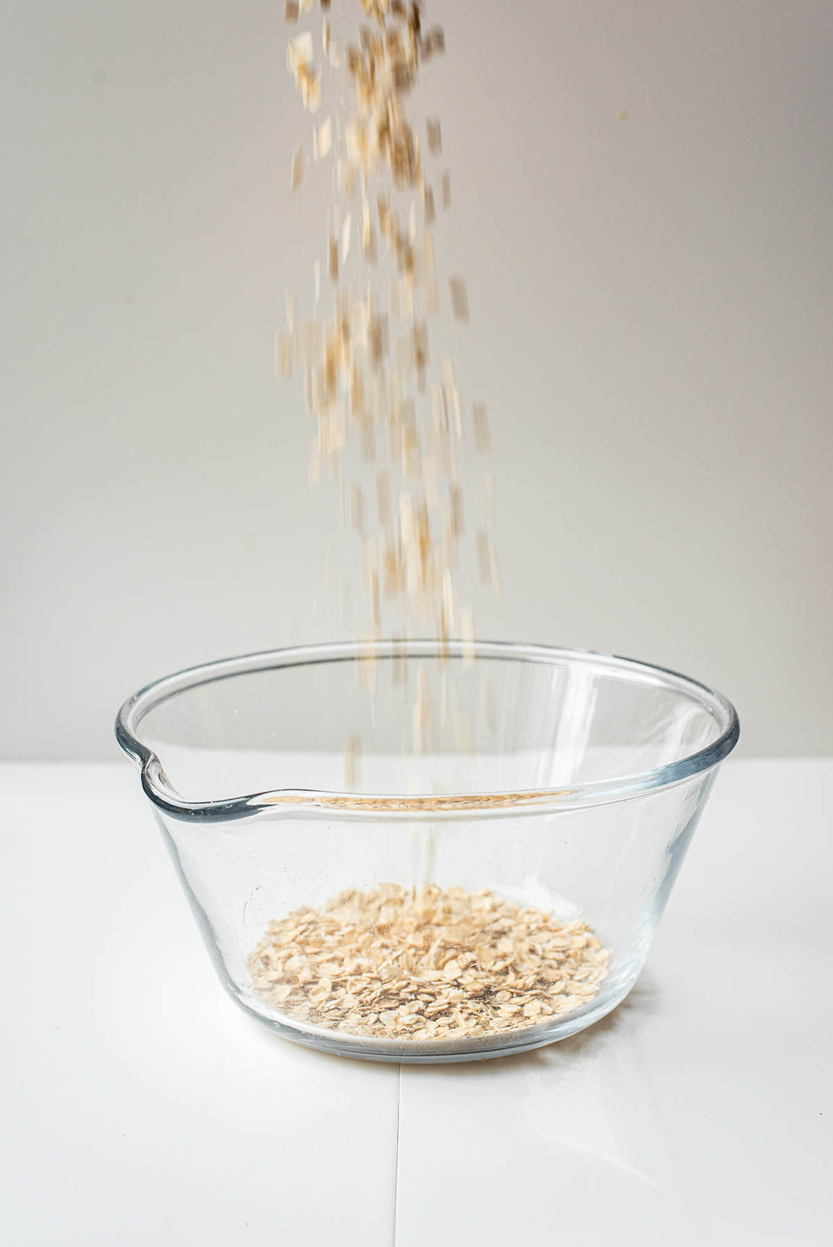 Oats being poured into a large glass bowl.