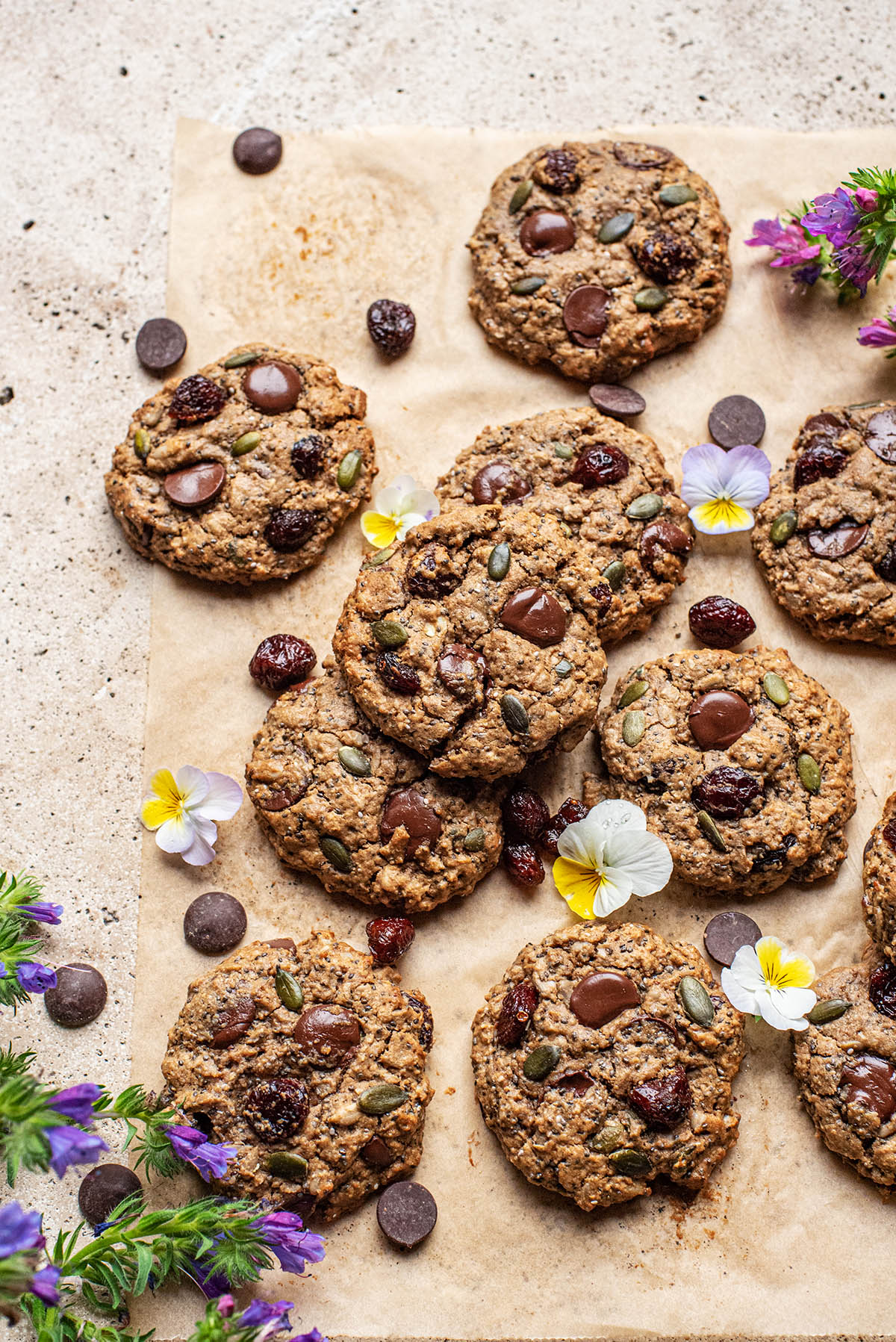 Several trail mix cookies on parchment paper with chocolate and dried cranberries.