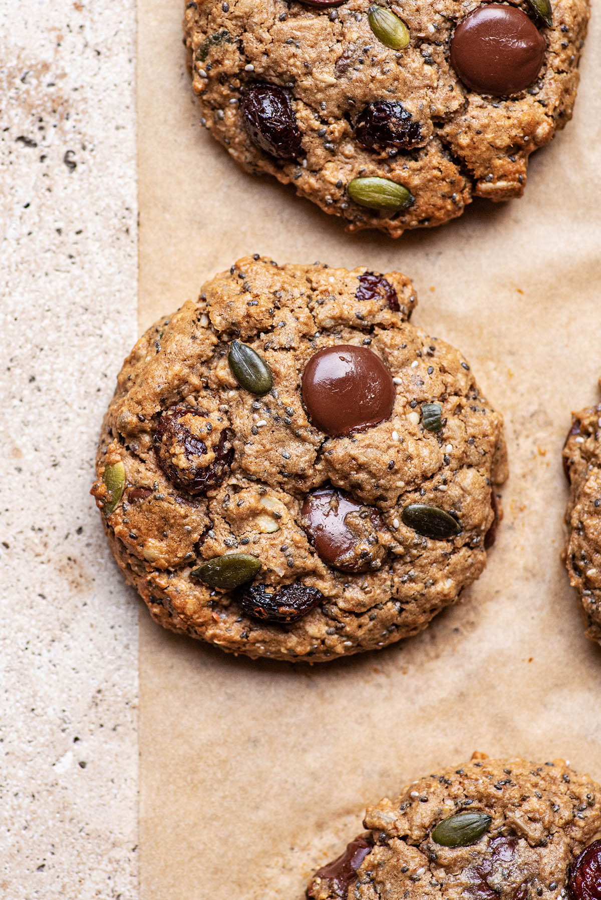 Close up of a cookie with seeds and chocolate.