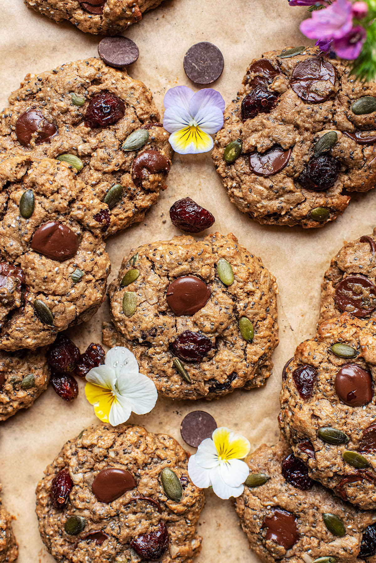 Trail mix cookies with chocolate, cranberries, and pansies, on parchment paper.