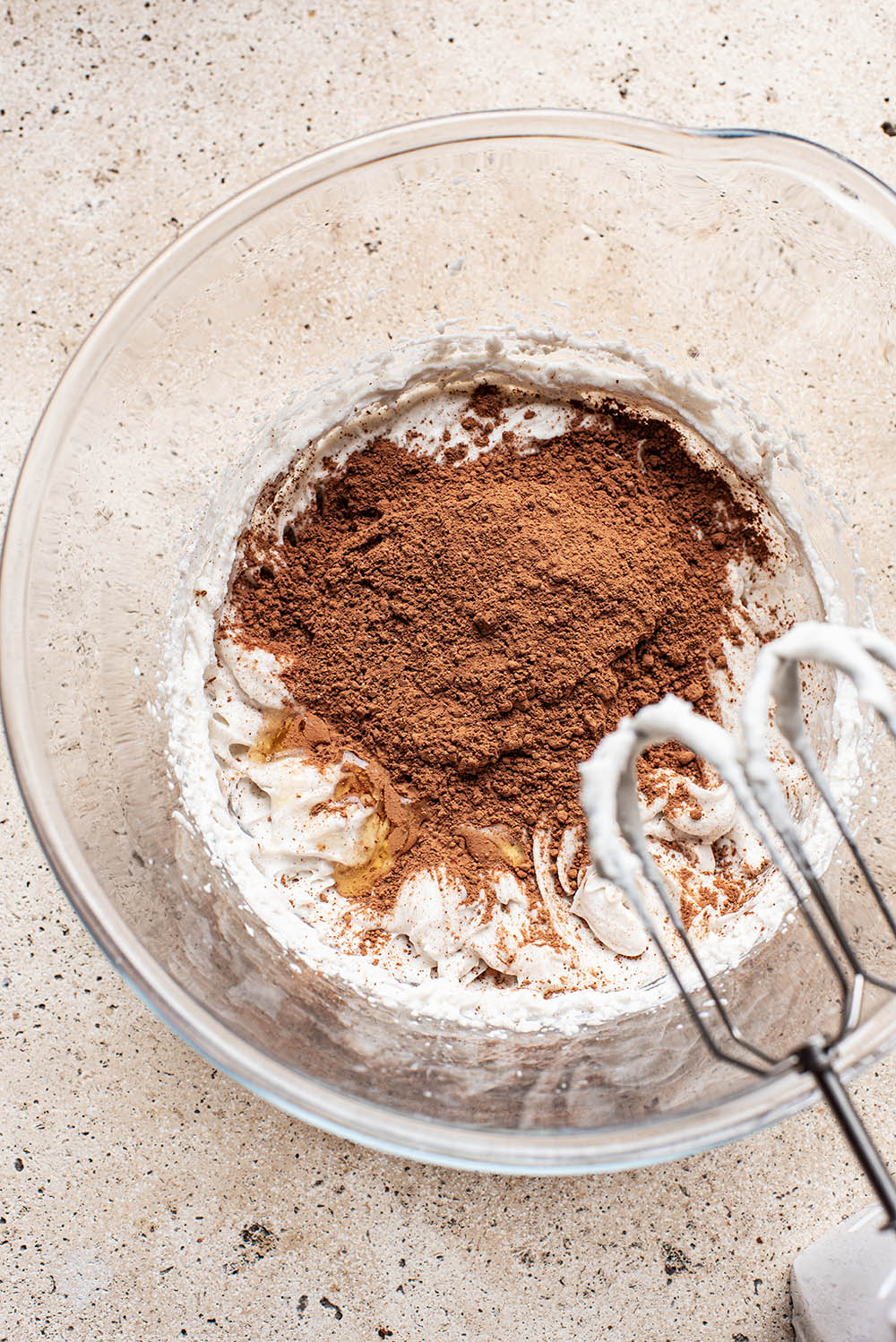Cocoa powder over coconut whipped cream in a large glass bowl.