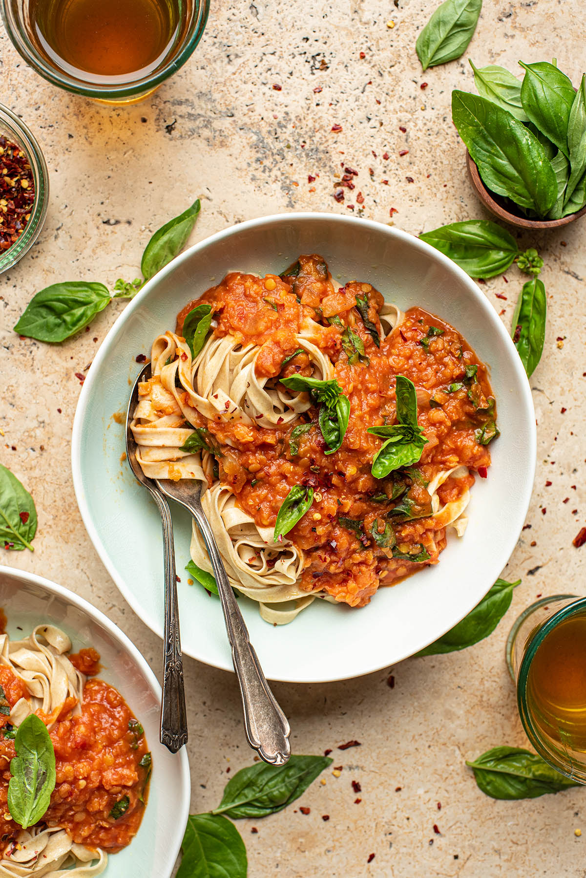 A bowl of lentil bolognese with pasta and basil.