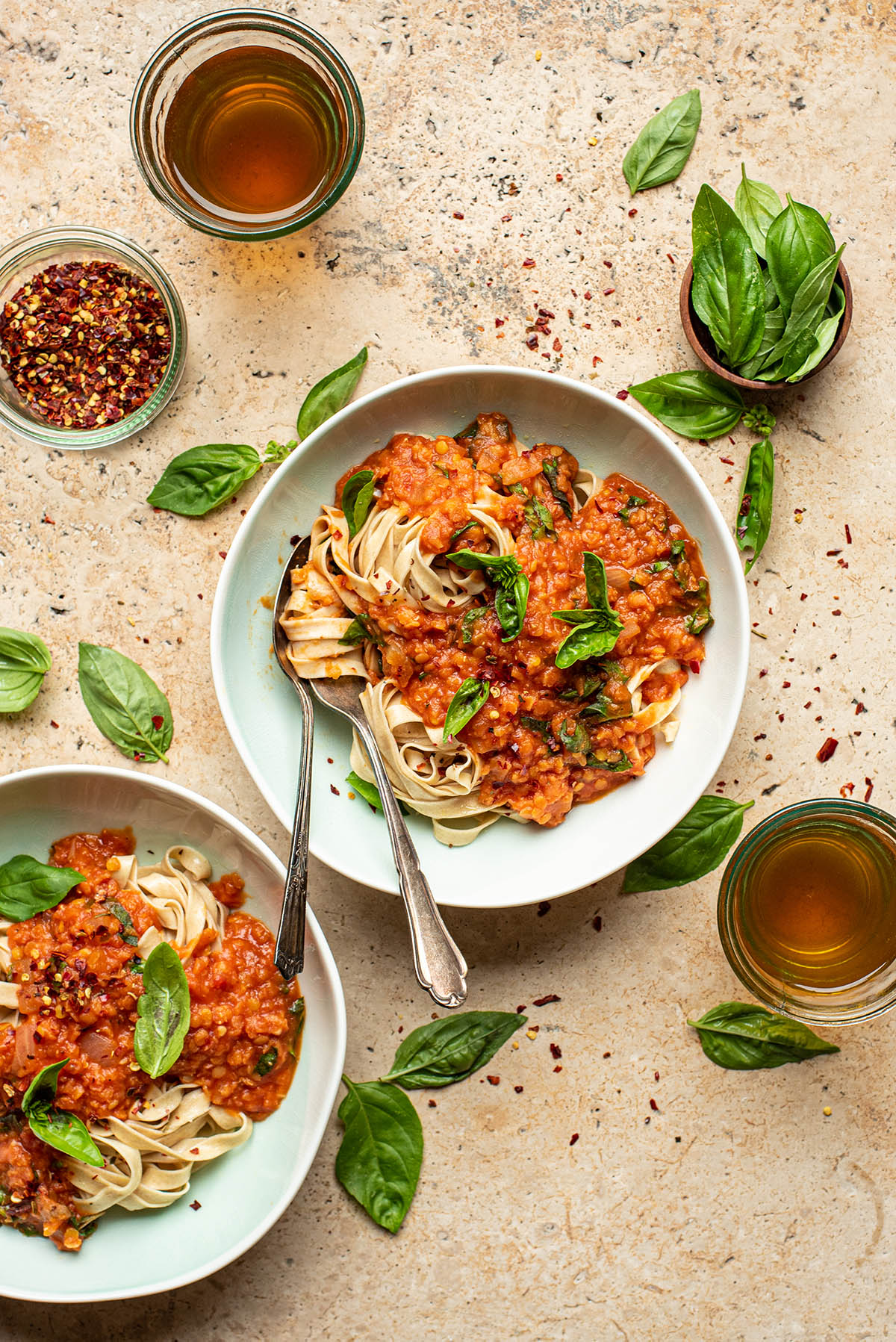 Two bowls of pasta topped with lentil tomato sauce and basil.