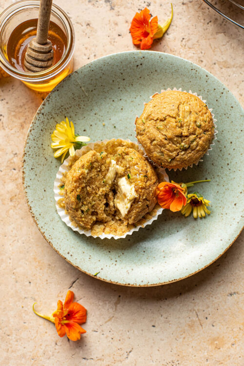 Halved muffin on a green plate with flowers and another muffin.