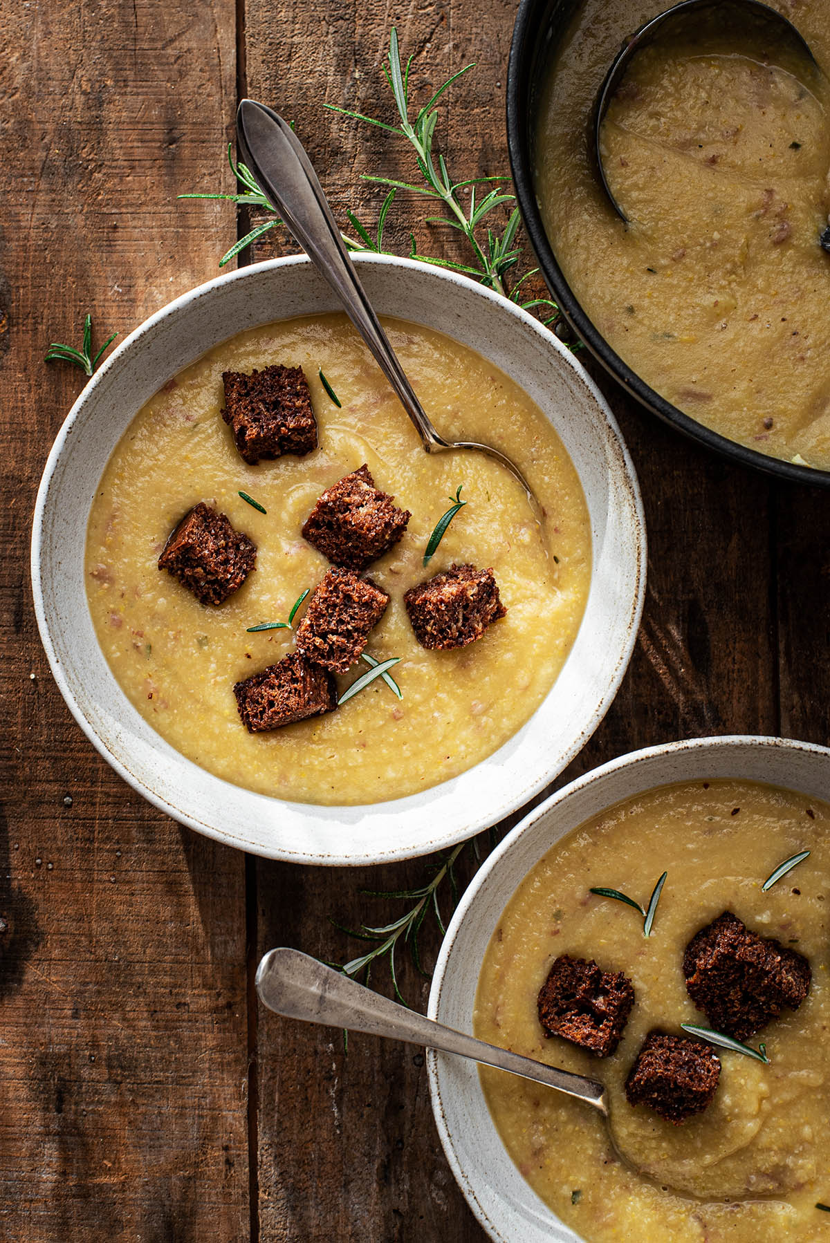 Bowls of cauliflower potato soup topped with rye croutons.
