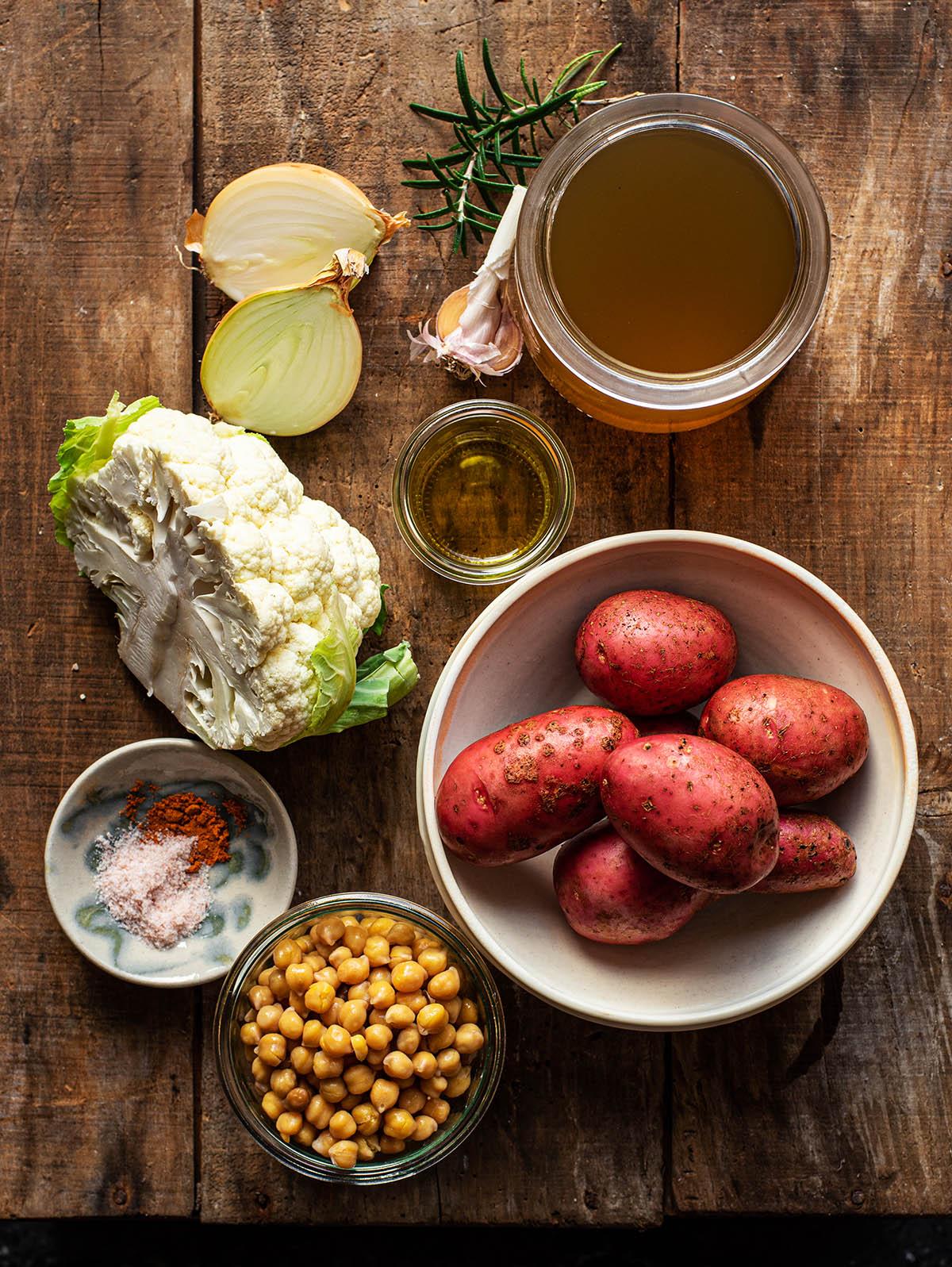 Cauliflower potato soup ingredients on a wooden board.
