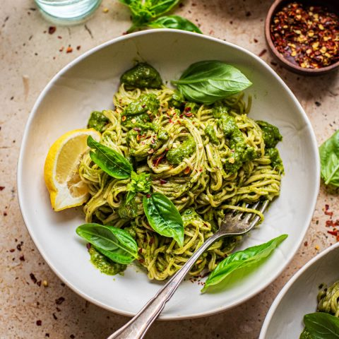 A bowl of pasta with green sauce and basil.