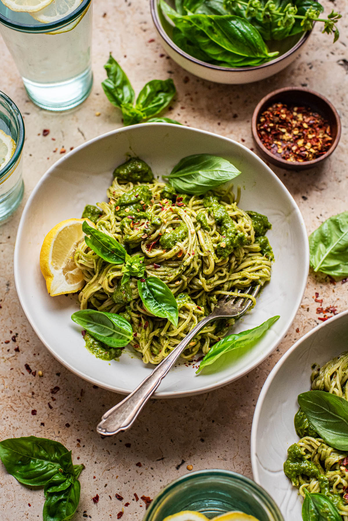 A bowl of pasta with green sauce and basil, with another bowl in the bottom right corner.