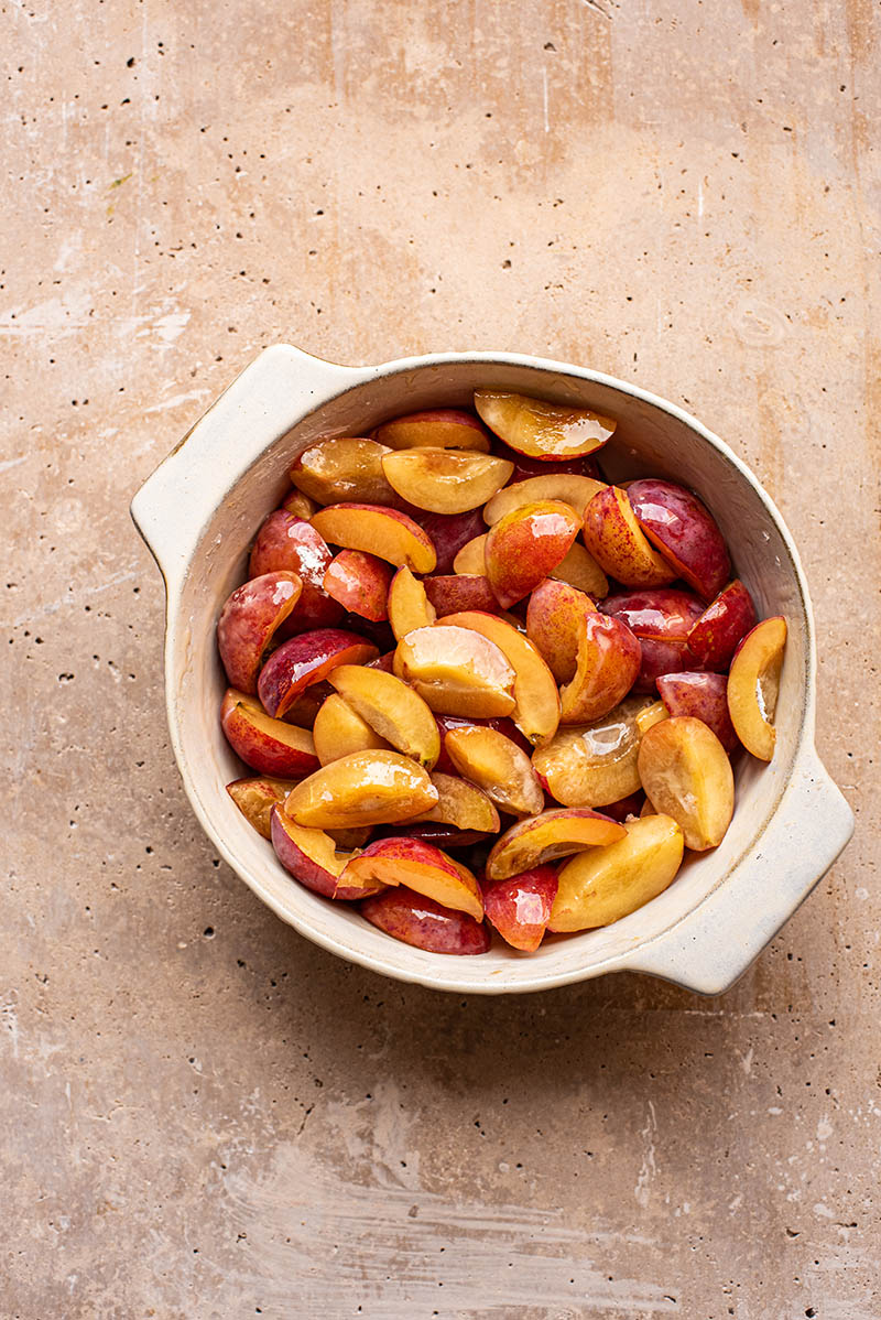 Quartered plums with filling ingredients in a ceramic baking dish.