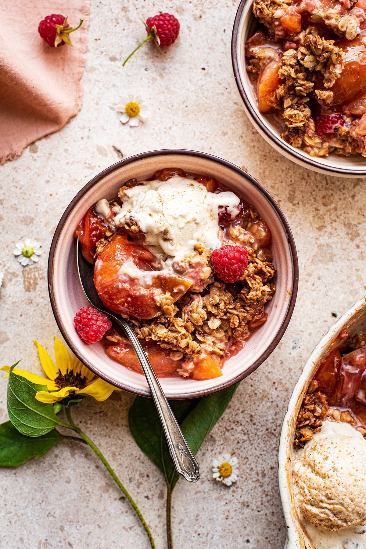 A small bowl of plum crisp with ice cream and raspberries.