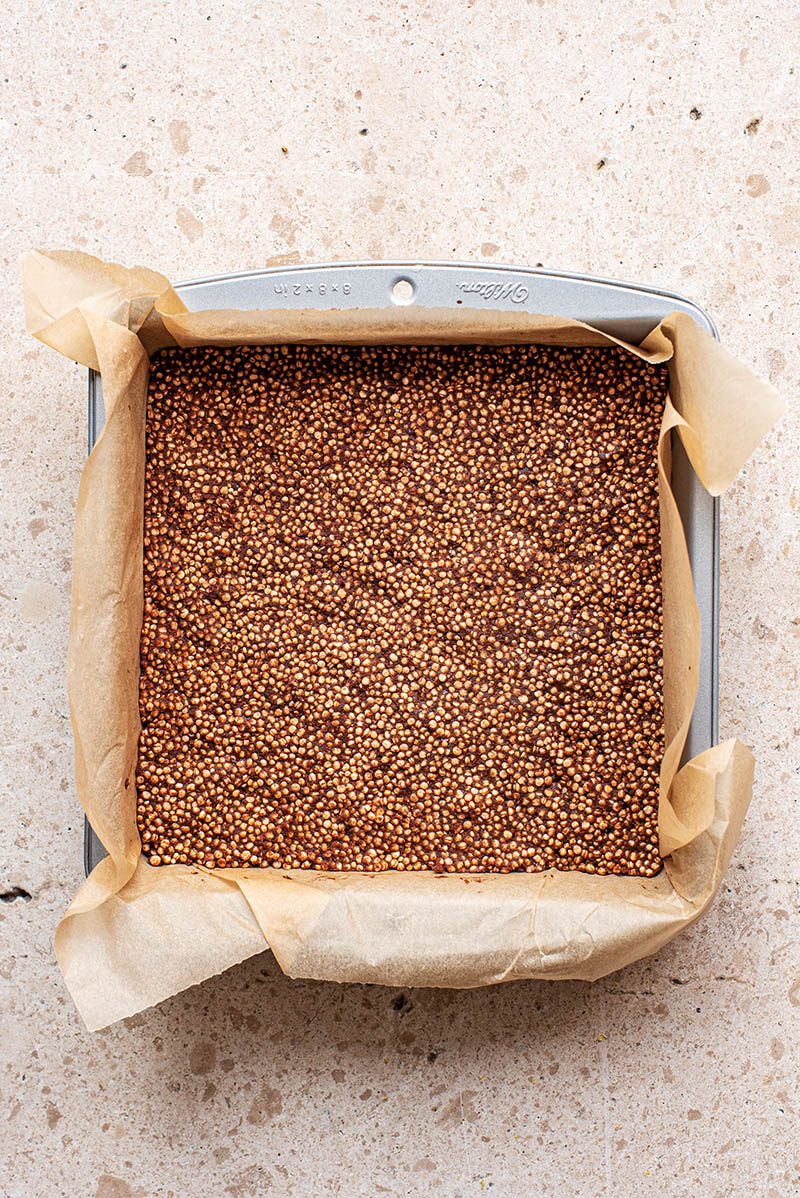 Puffed quinoa snack bar mixture pressed into a square baking tin.