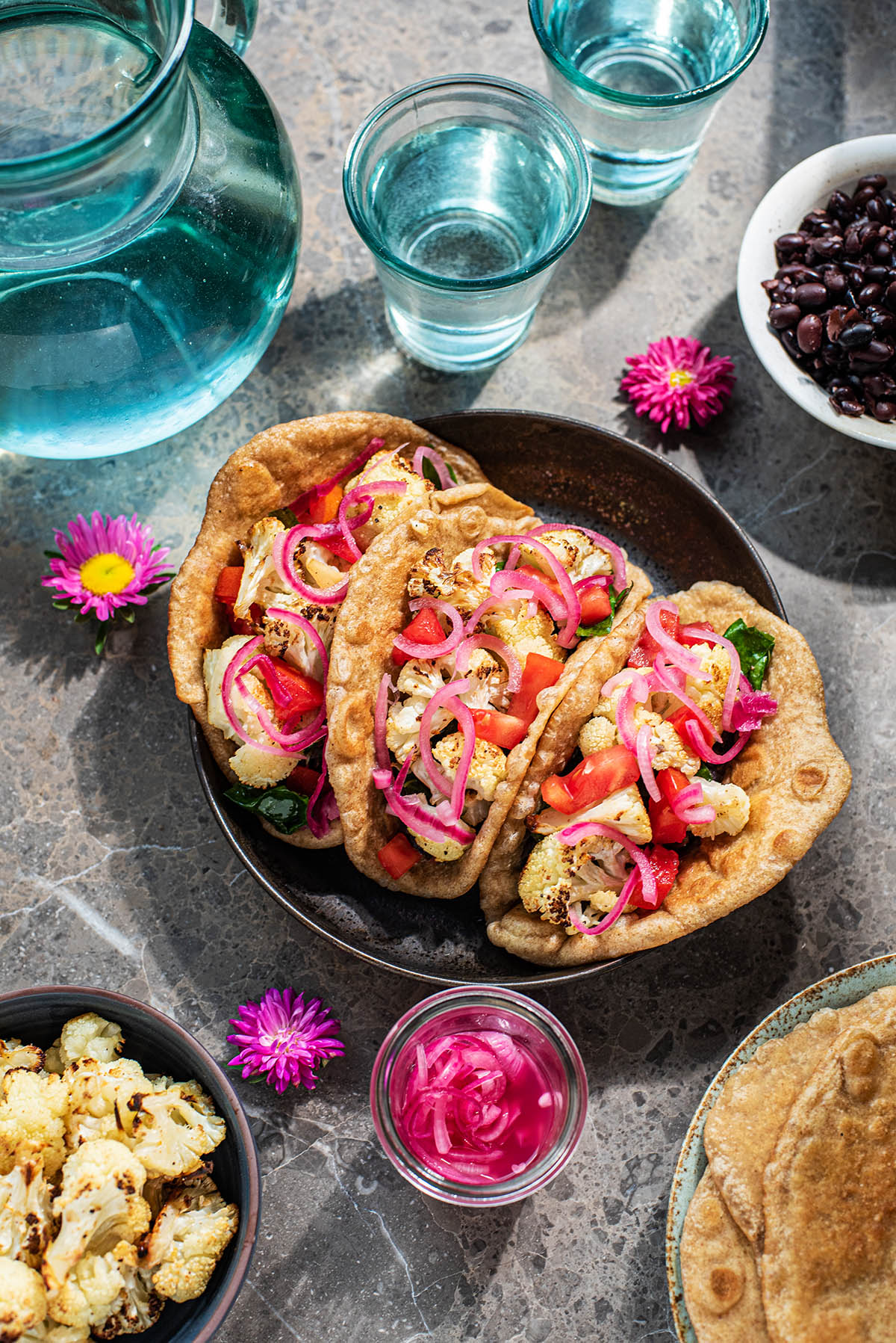 Three cauliflower tacos topped with pickled red onions.