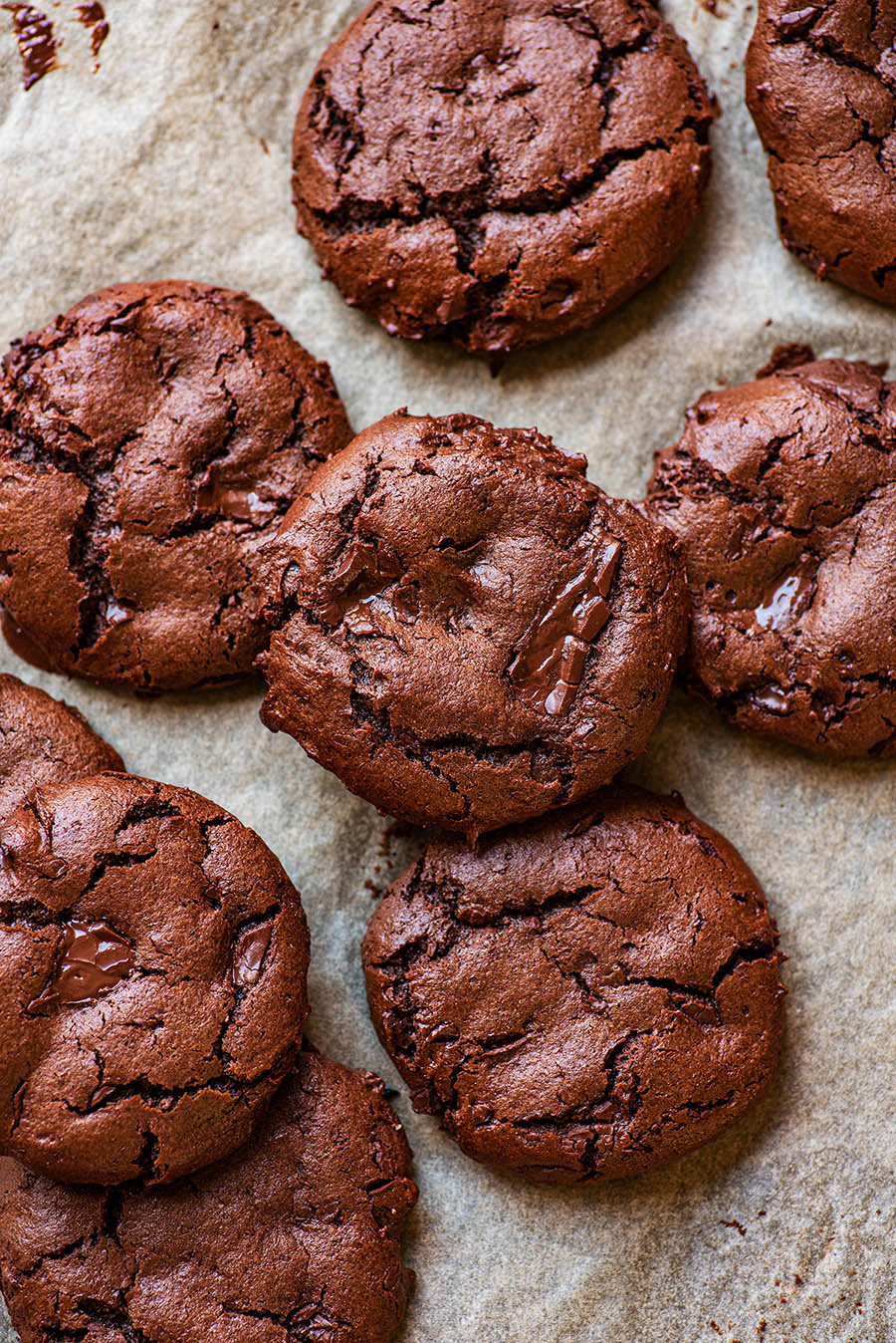 Chocolate cookies piled on a baking sheet.