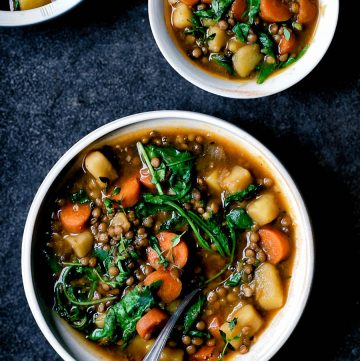 Three bowls of lentil, carrot, and potato stew, two partially in shot.