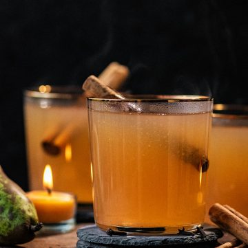 Cider in three glasses with cinnamon sticks.