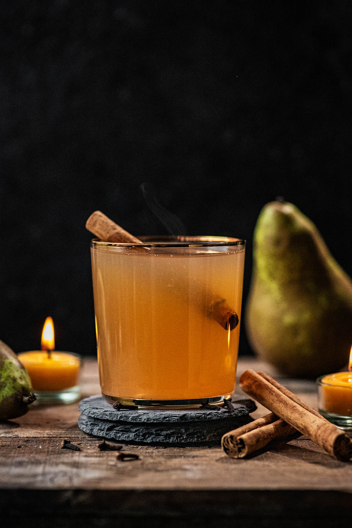 A glass of pear cider with a cinnamon stick and lit candle.