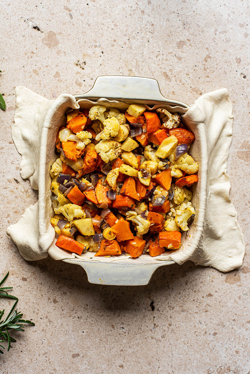 Vegetables places into a baking dish with pastry overflowing the sides.