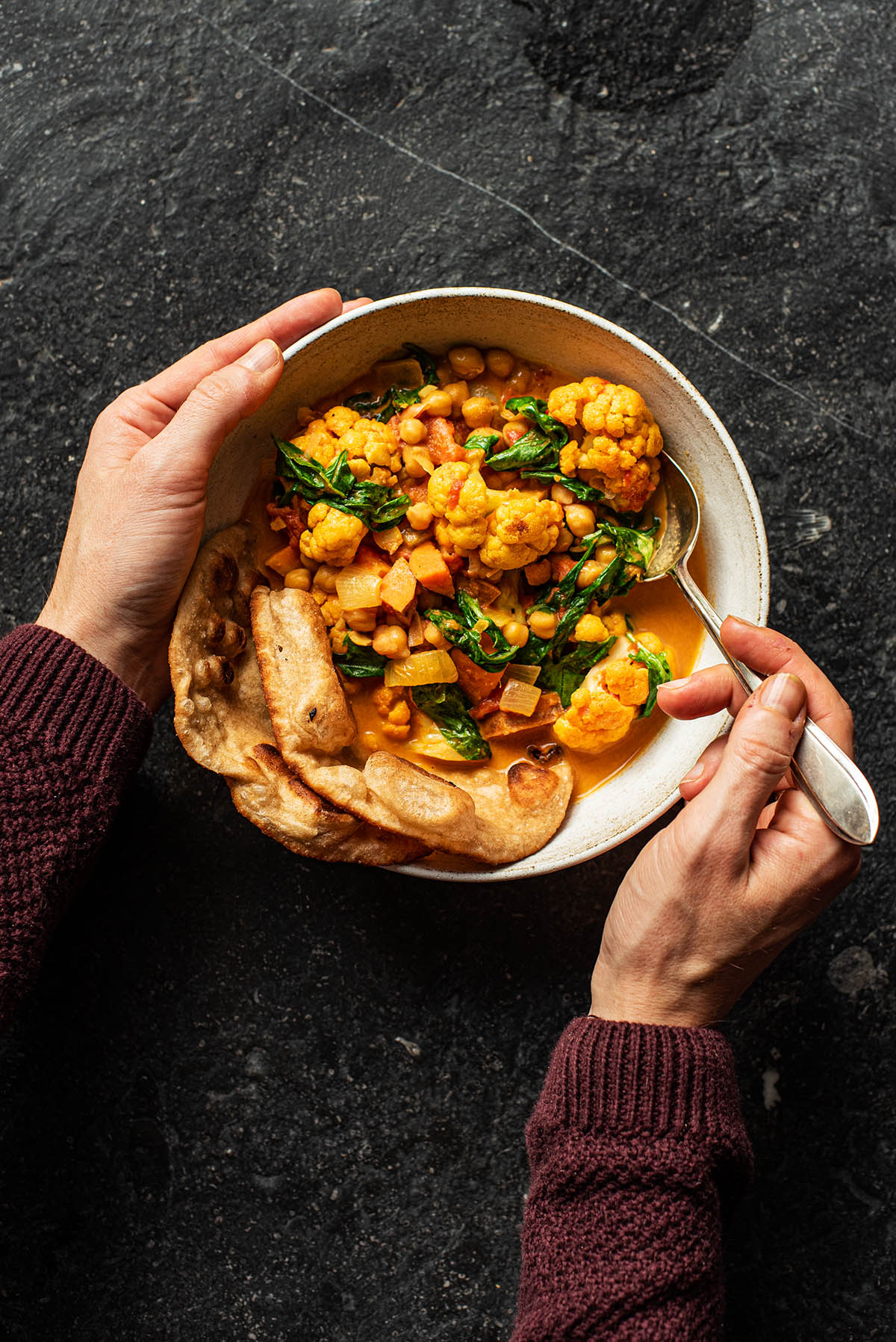 Woman's hands lifting a spoon in the curry.