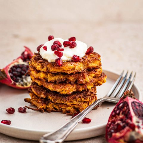 A stack of several sweet potato latkes topped with yogurt and pomegranate seeds.