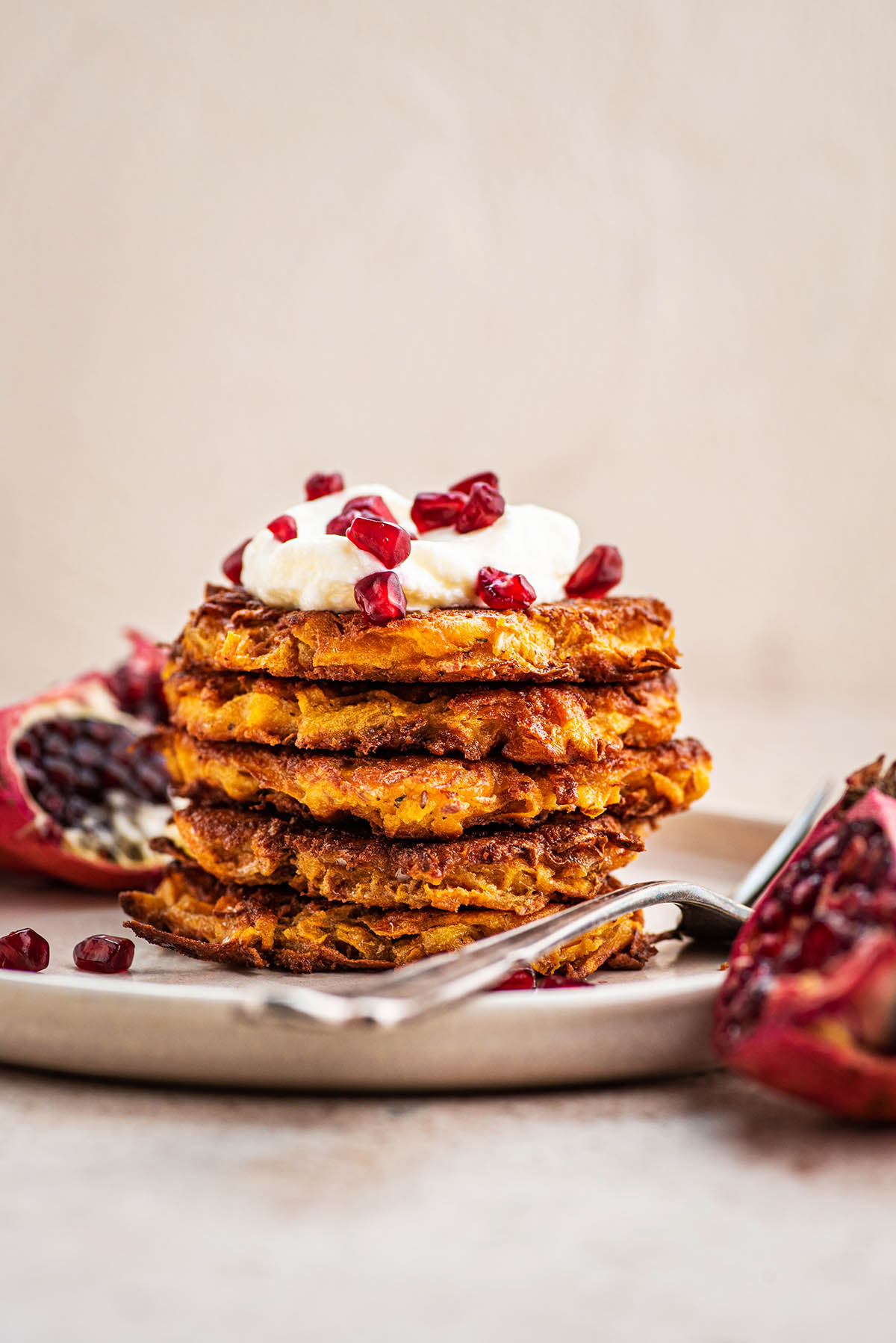 Stack of latkes on a plate with a fork.