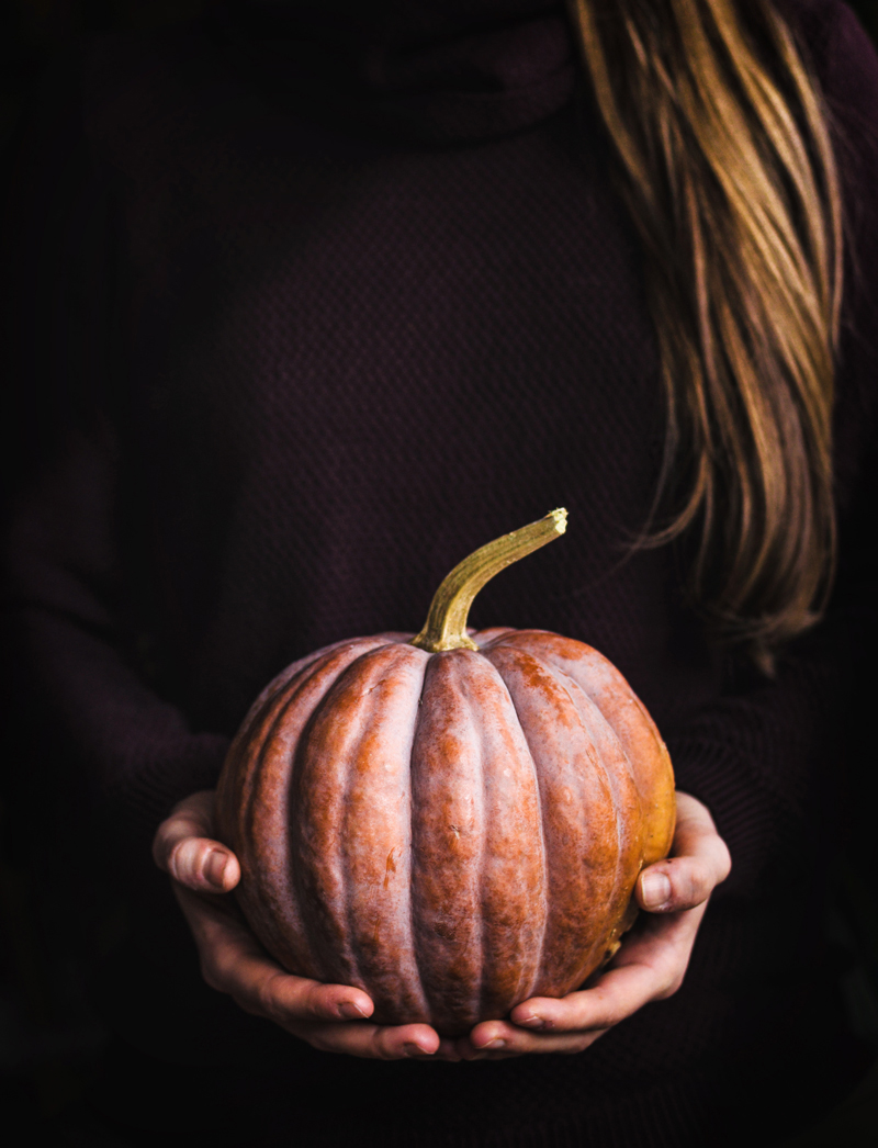 Woman with long hair holding a pumpkin.