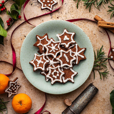 A plate of cookies surrounded with spices, oranges, ribbon, and greenery.
