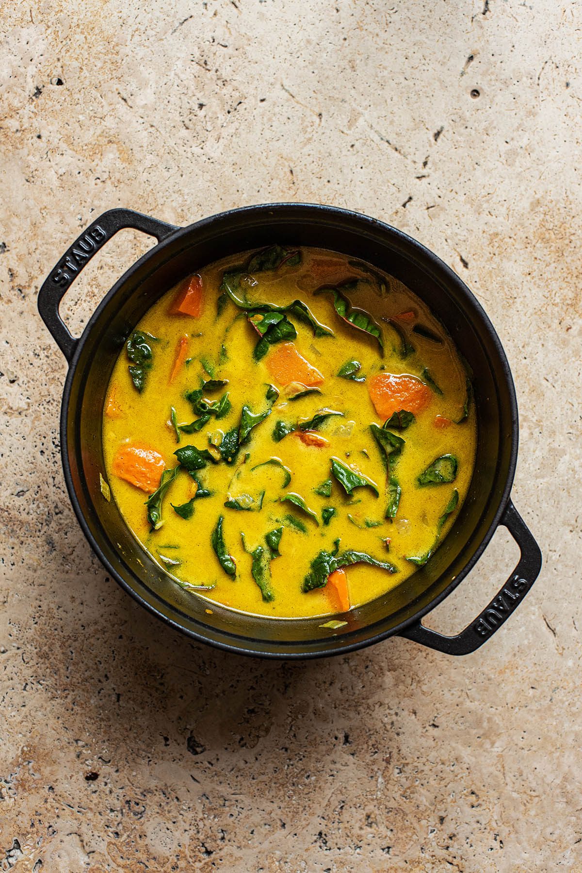 Pumpkin curry with greens in a large pot.