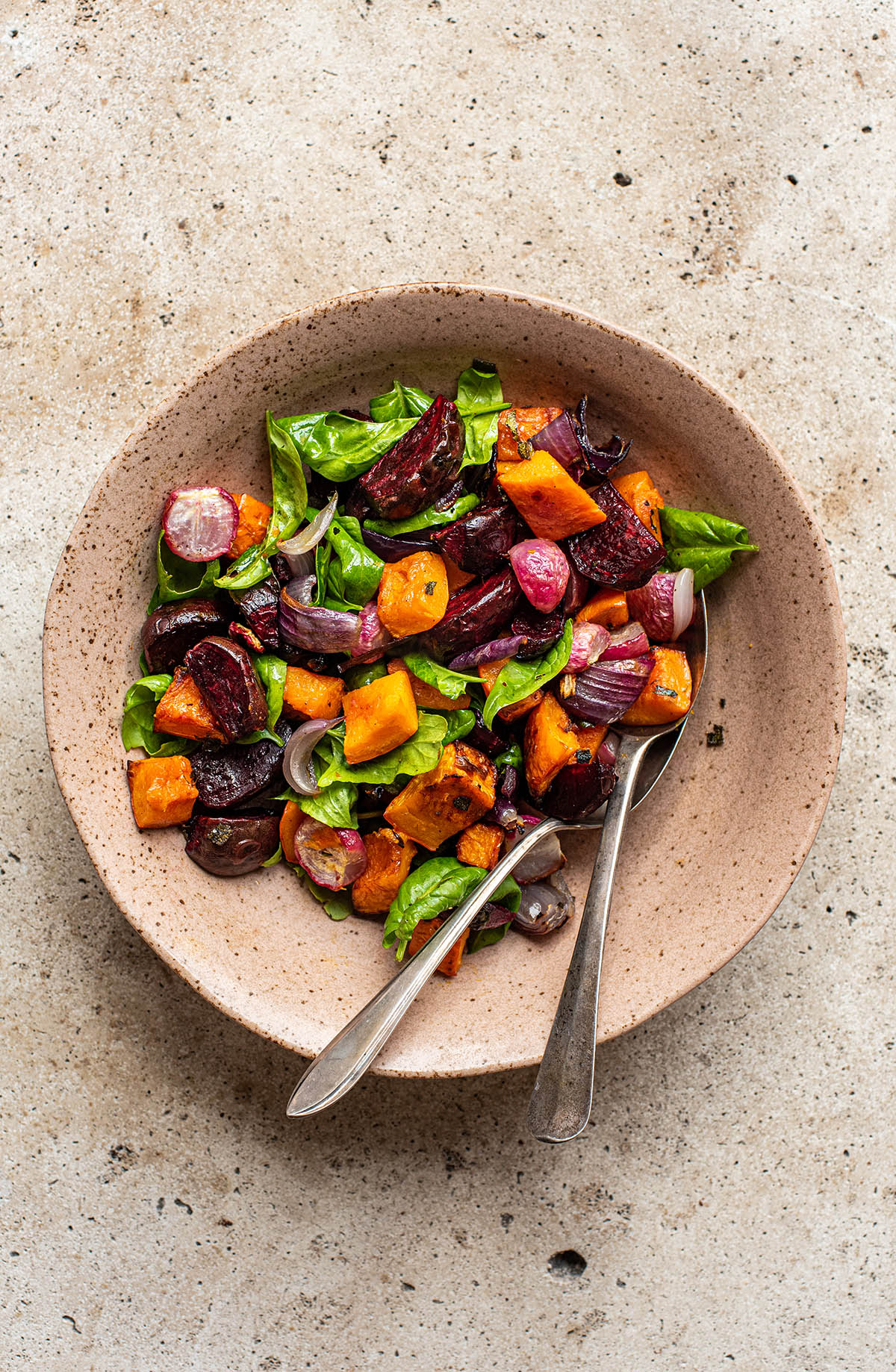 Roasted vegetables added to greens in a large bowl.