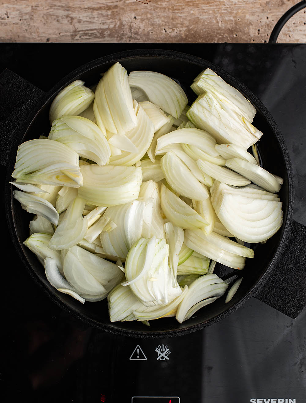 Raw onion slices added to the pan.
