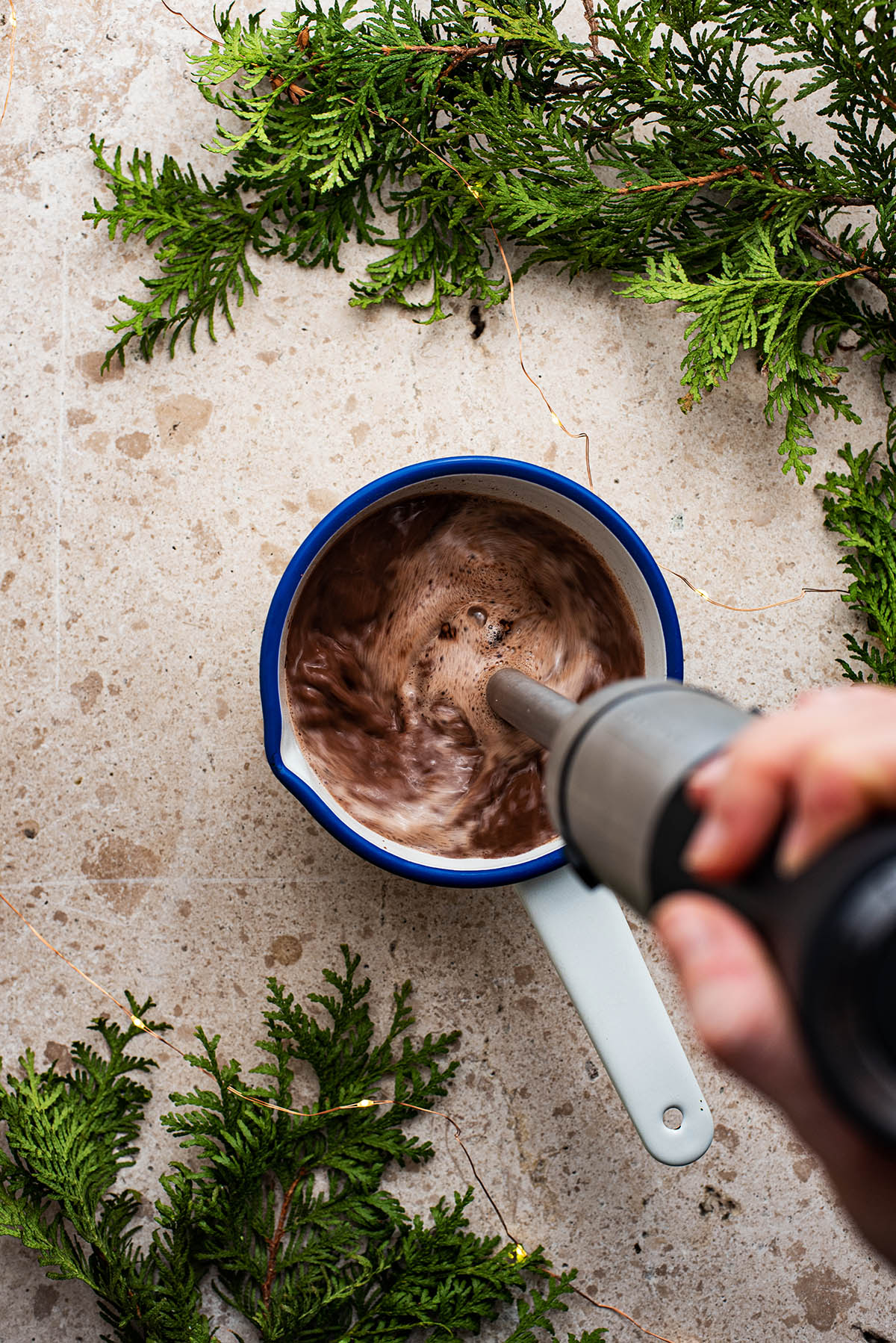 Hot chocolate being blended with an immersion blender.