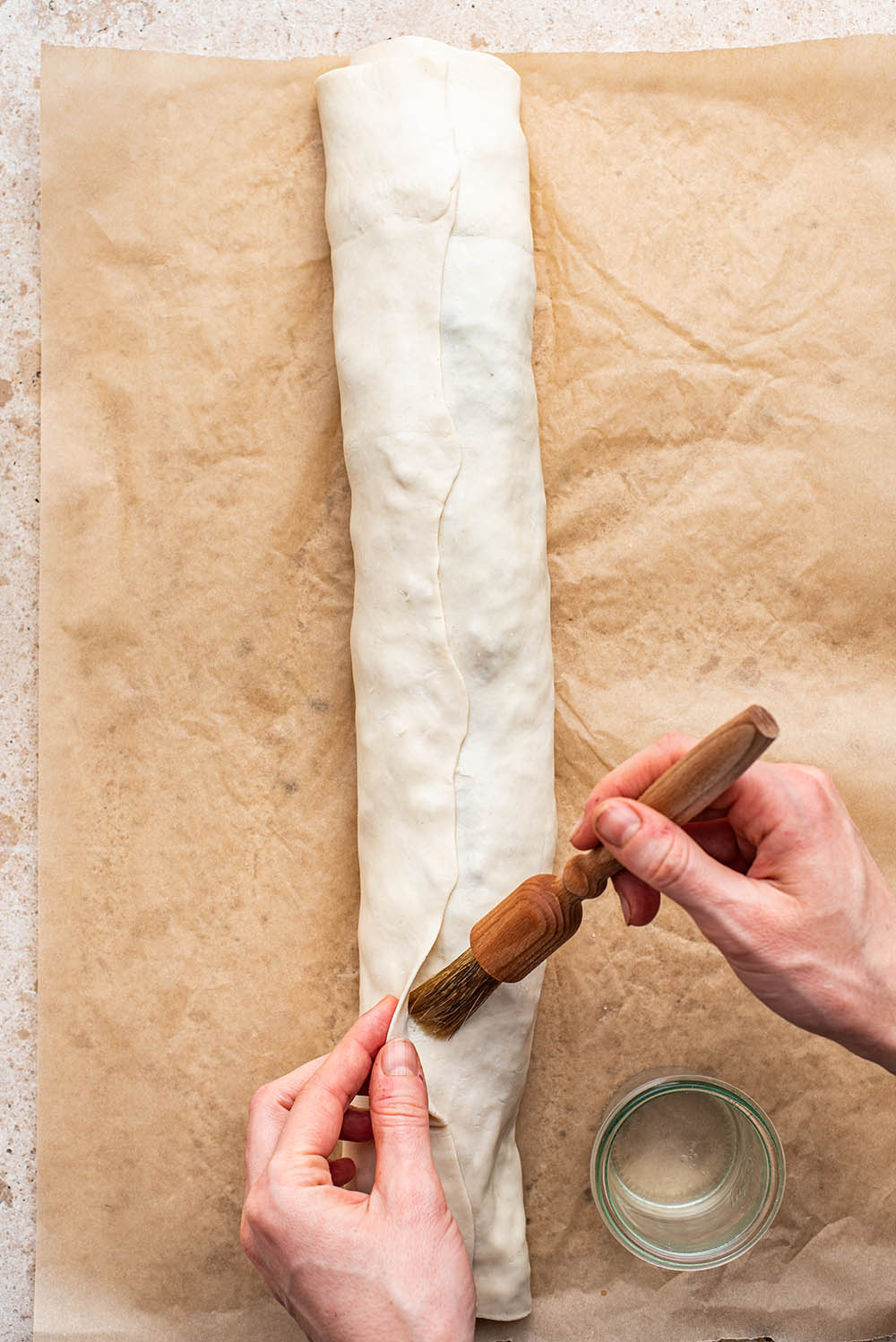 Brushing the seam with water to seal the pastry.