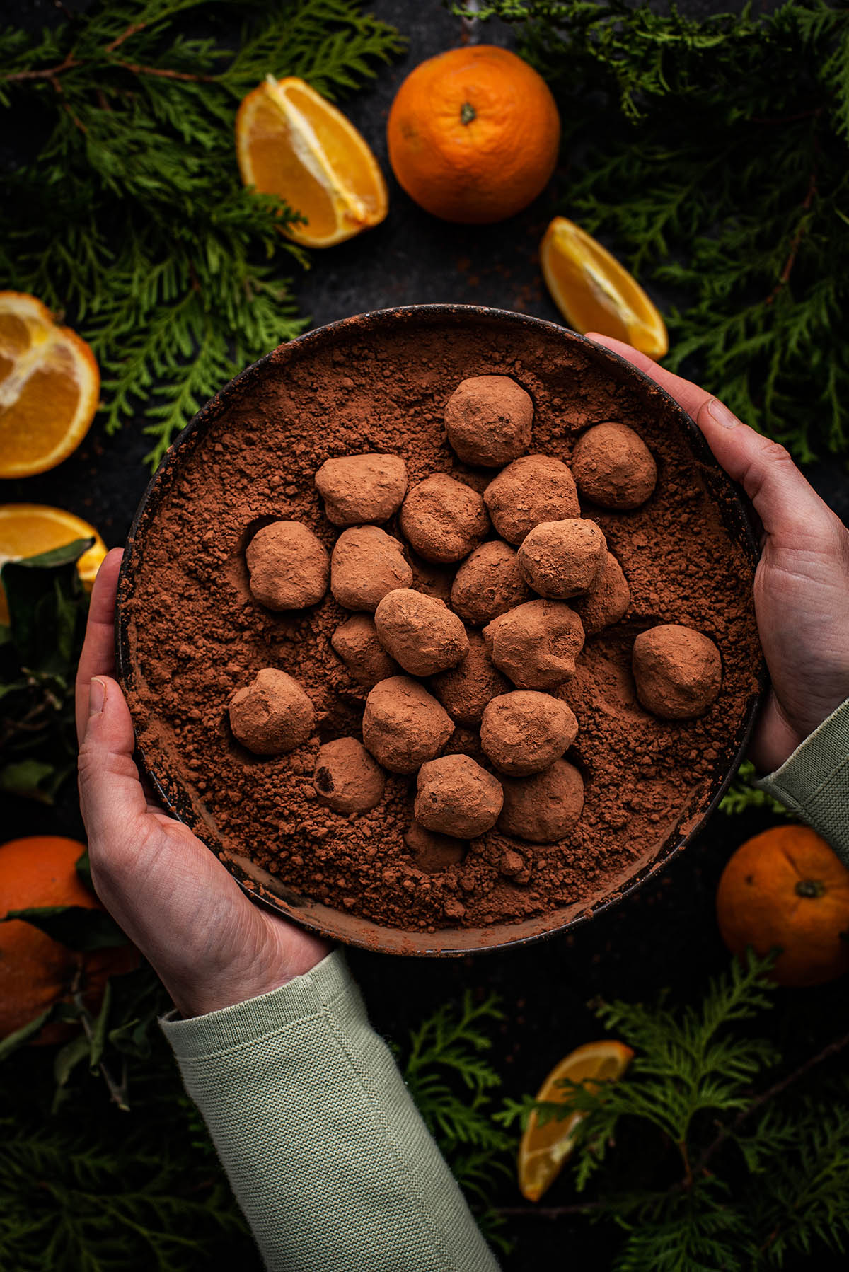Hands holding a bowl of truffles.
