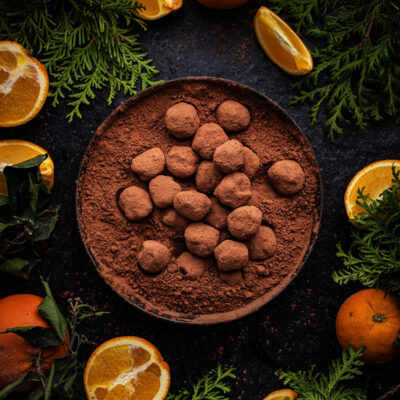 Bowl of truffles surrounded by oranges and greenery.