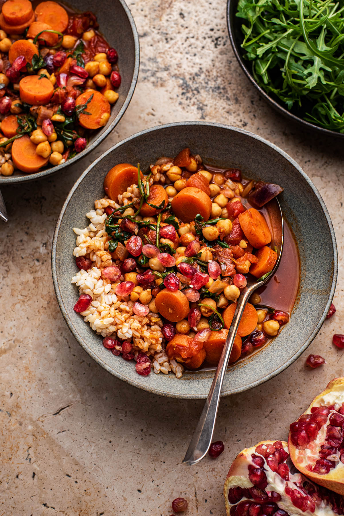Two bowls of stew, with a bowl of greens and pomegranate.