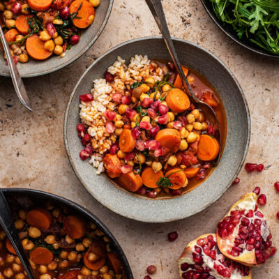 Two bowls of carrot chickpea stew with greens and pomegranate.